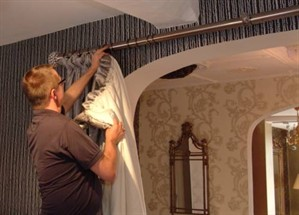 man_fitting_curtains_299x215