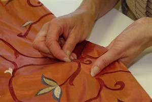 person_sewing_material_300x201